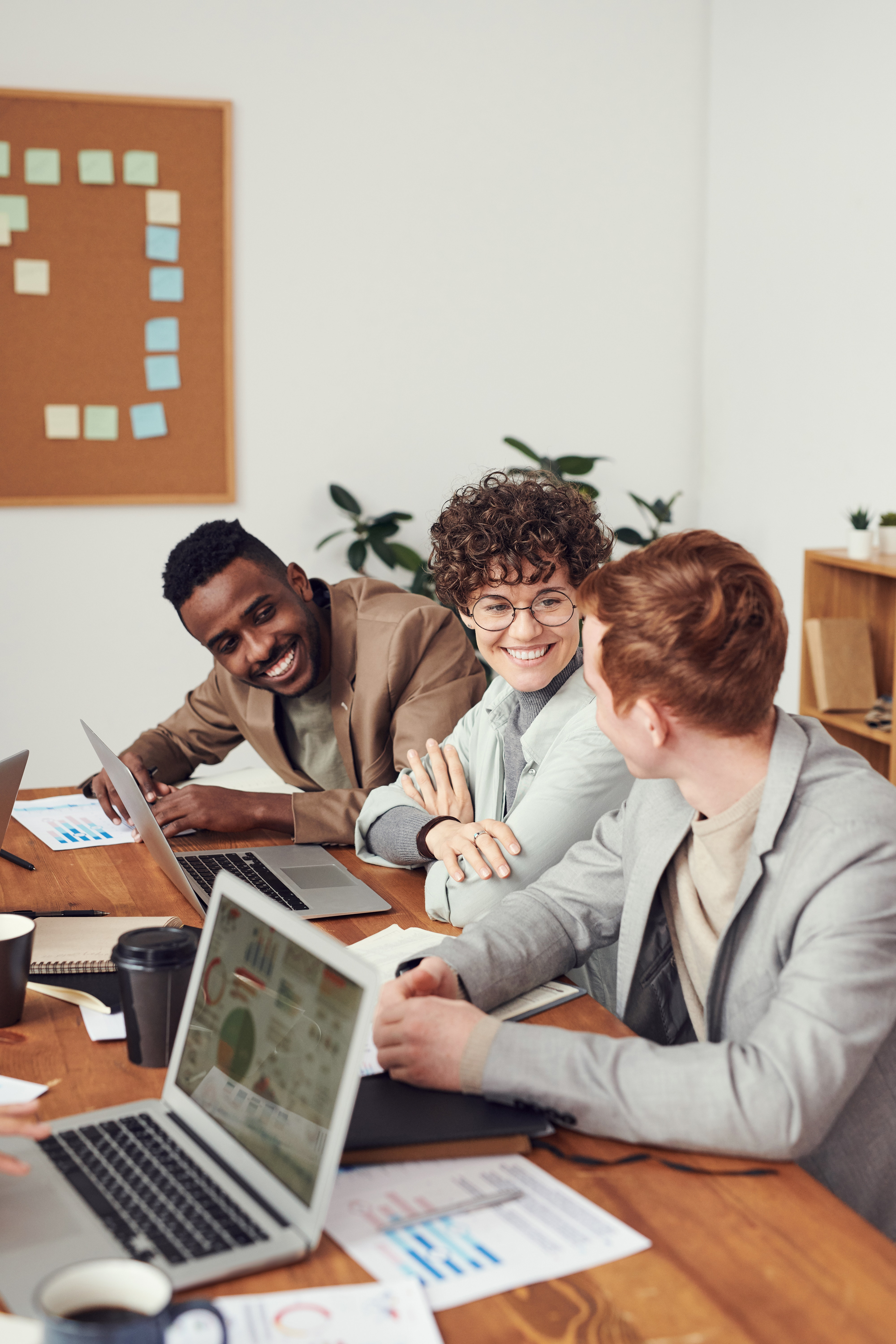 Three people smiling and working together as a team on a project.