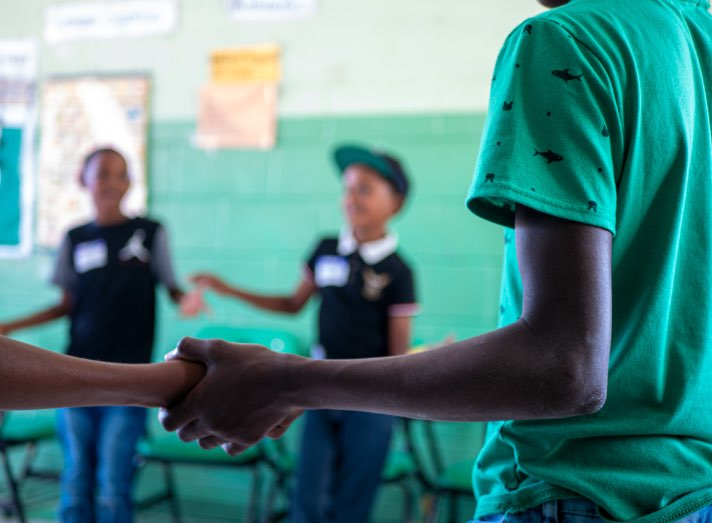 Kids holding hands in a classroom