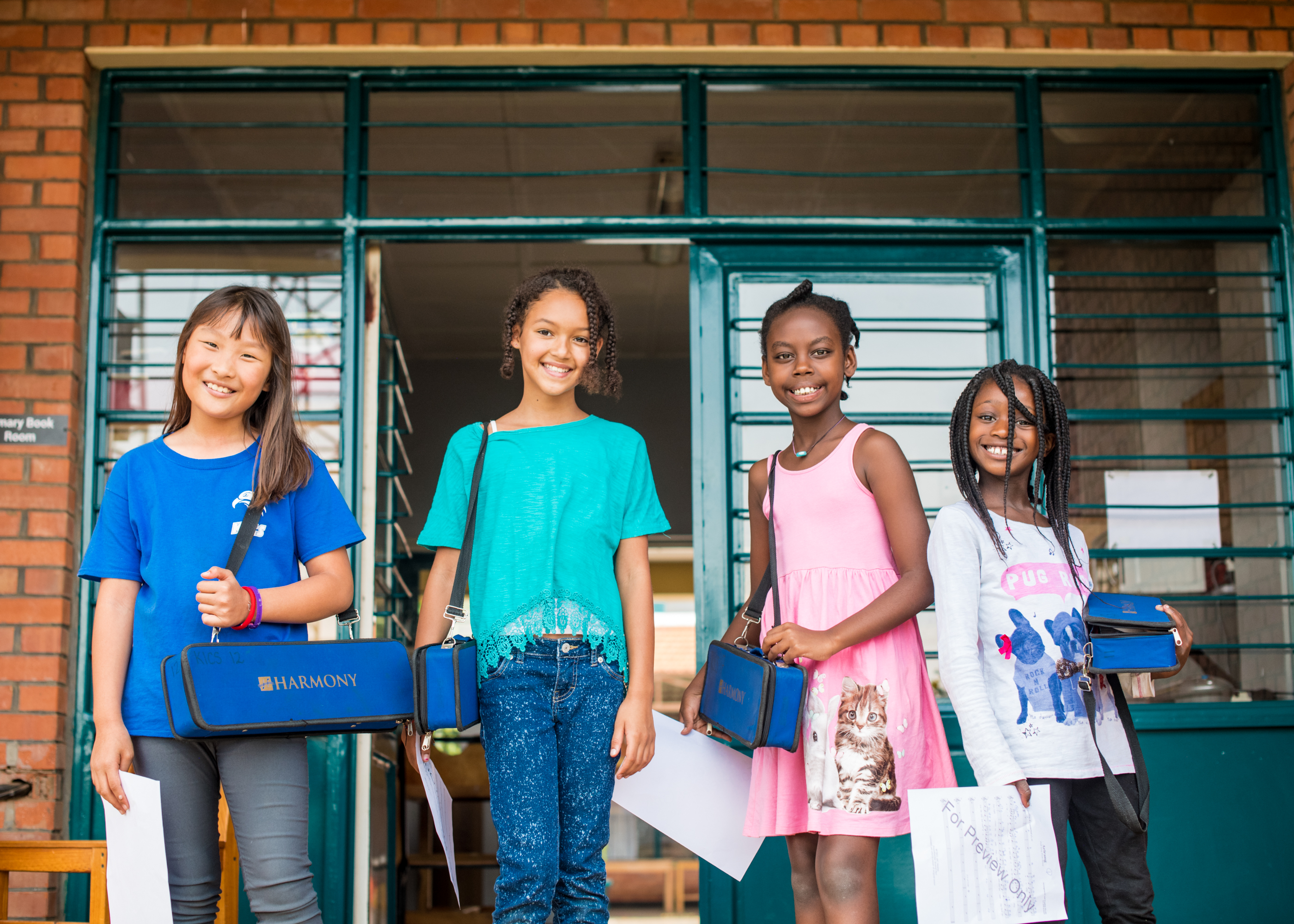 Children smiling in front of the entrance to their classroom
