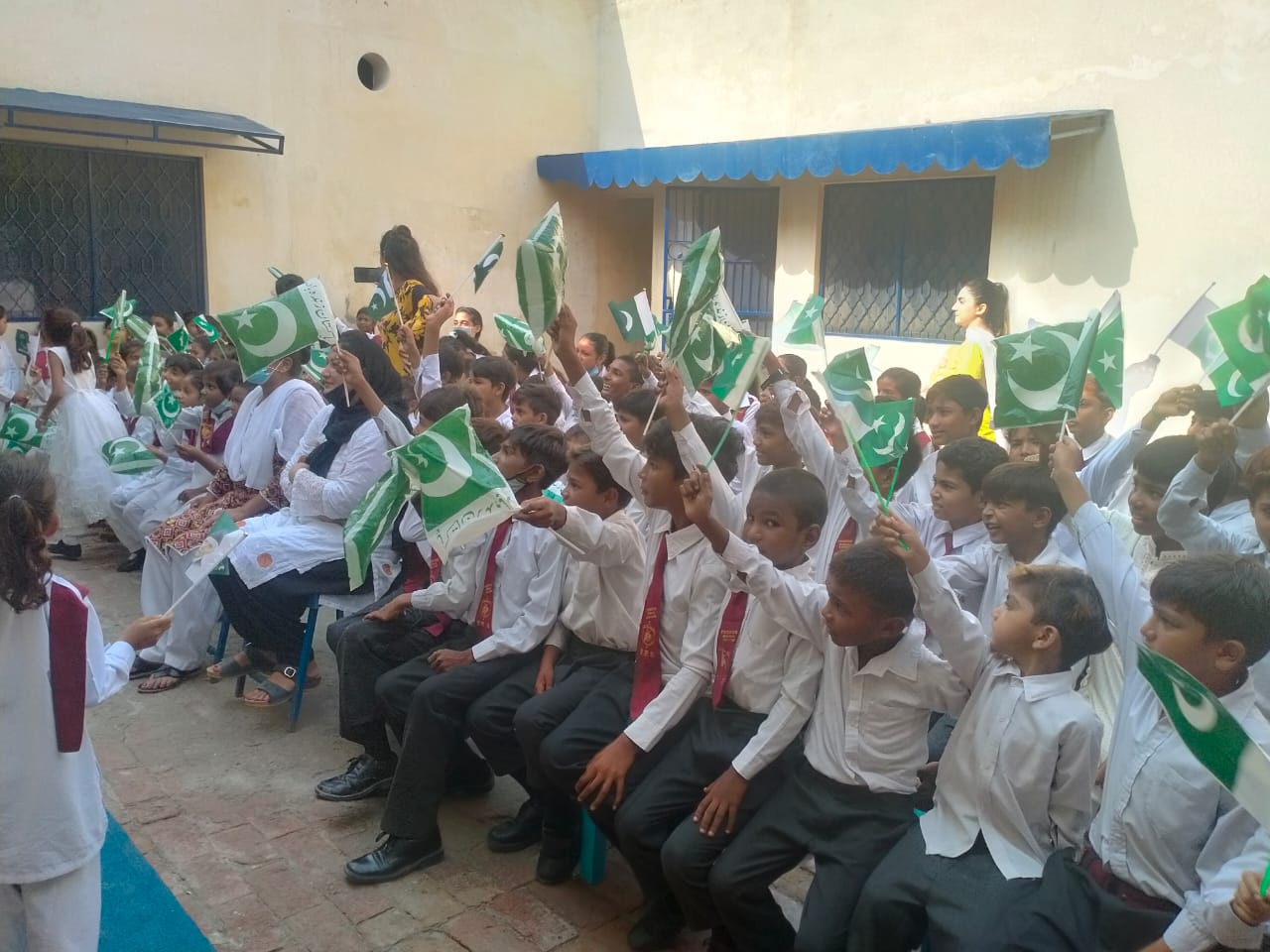 Students seated, each raising the pakistan flag