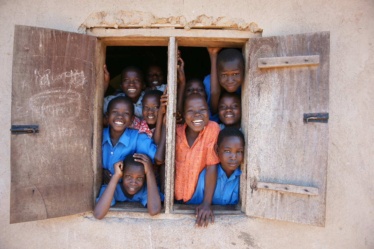 Children happily posing for a picture on the window