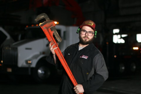 JE-CO Truck & Trailer mechanic holding a HD wrench