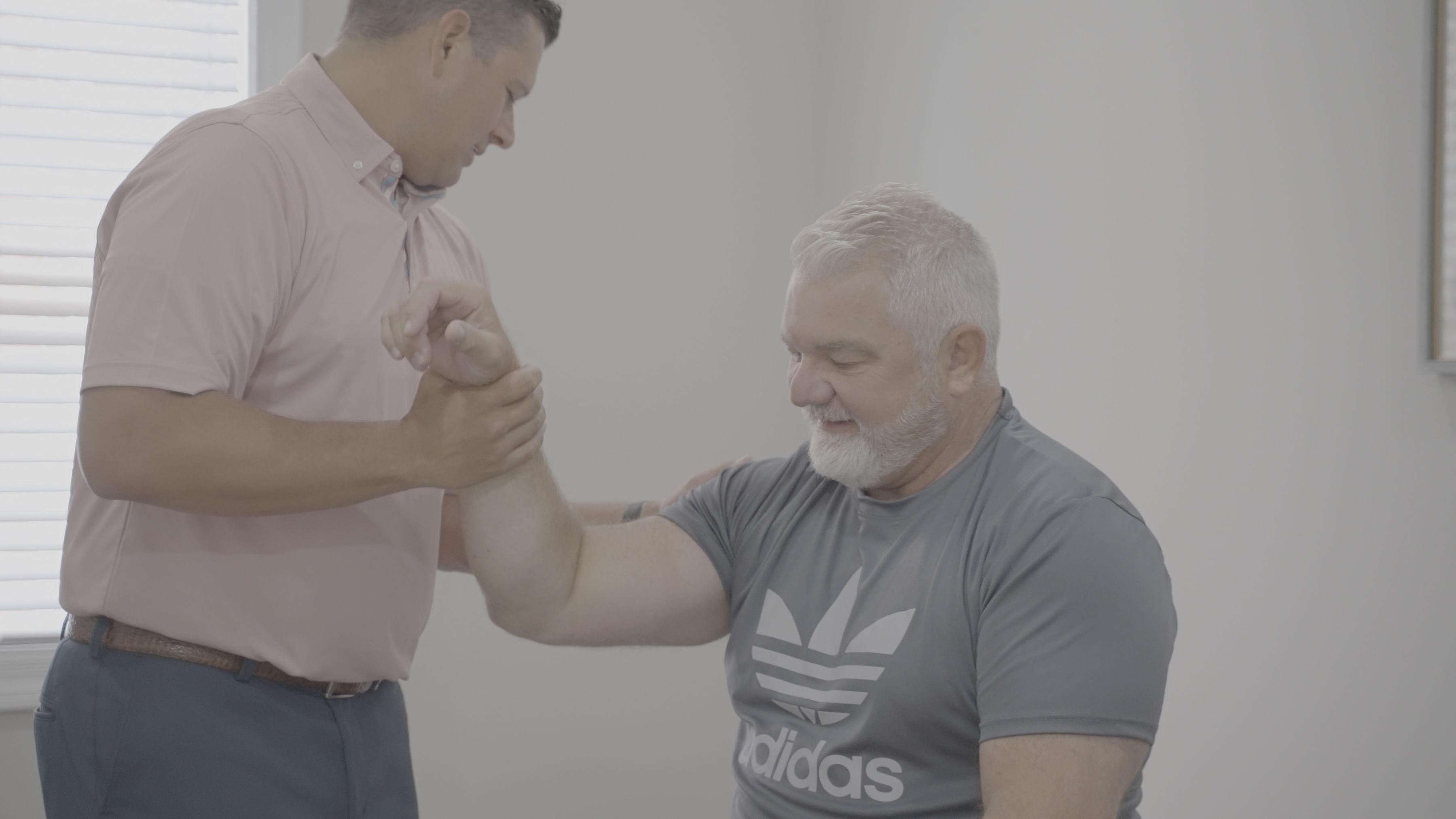 Dr. Paul holding the patient's arm