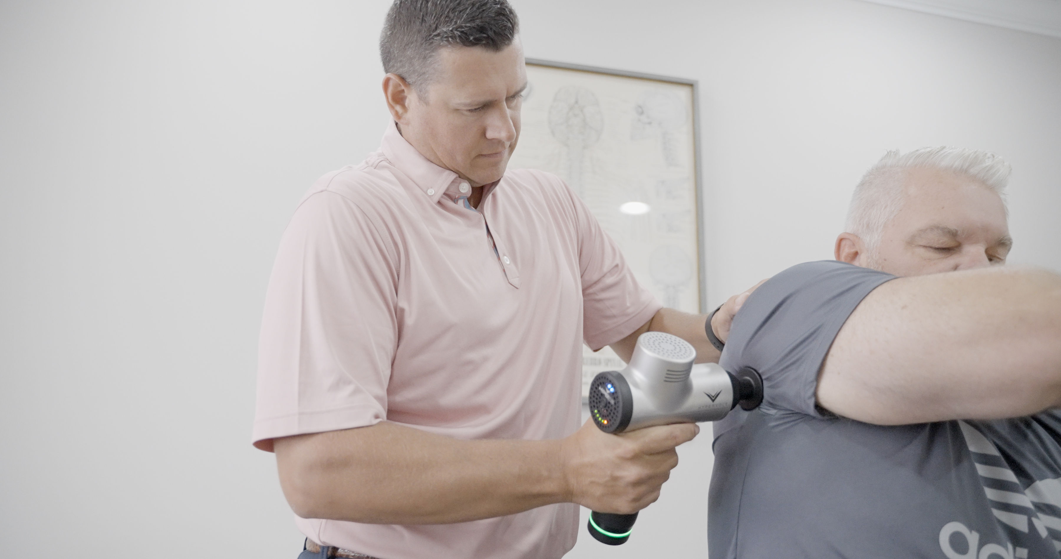 Dr. Paul using hammer-like device to patient