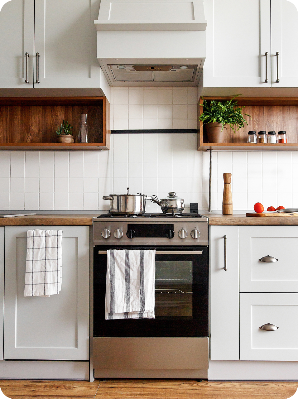 Clean kitchen with white cabinets and a stainless steel stove
