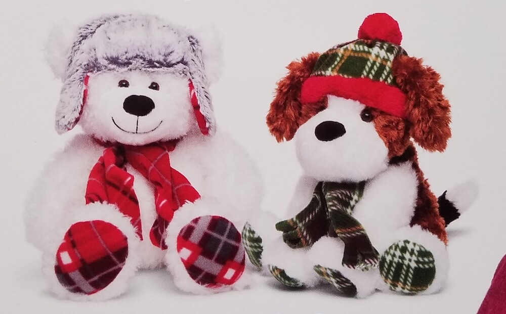 Two stuffed animals: a bear and a dog dressed in winter accessories