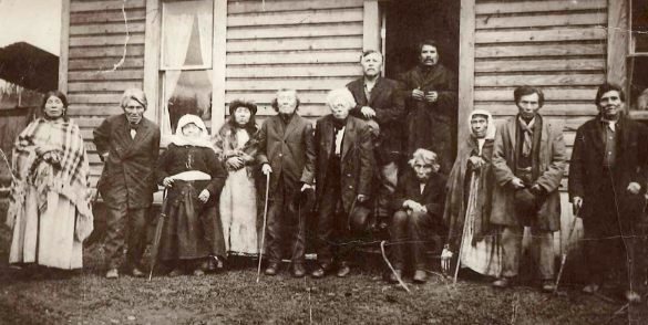 A sepia-toned image of Muckleshoot Indian Tribe members standing in front of a house on the reservation, circa 1850s.