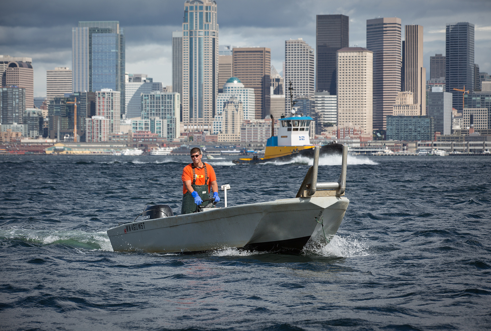 A small fishing boat with Muckleshoot Indian Tribe members travels across Elliot Bay, with the Seattle skyline in the background.