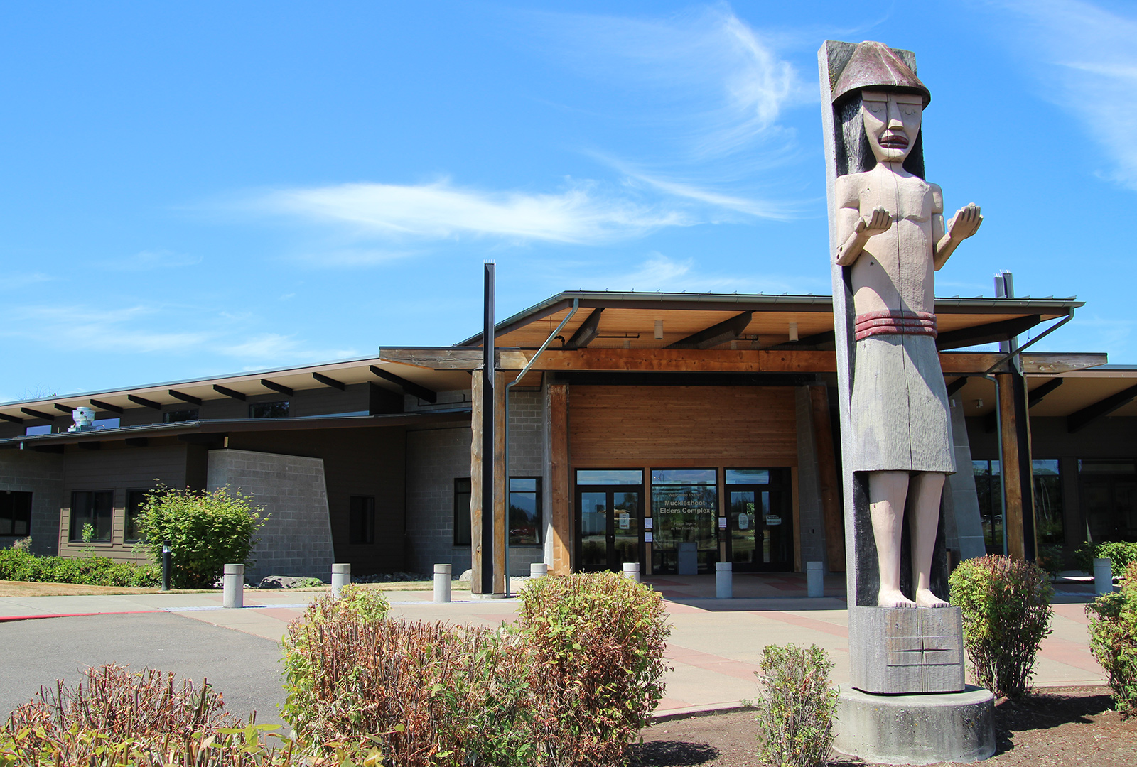 An architecturally-modern center for Muckleshoot Indian Tribal elders  stands against a bright, blue sky. A large totem pole stands in front of the center.