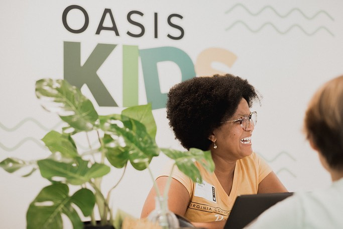 A woman checking kids in at Oasis Kids.