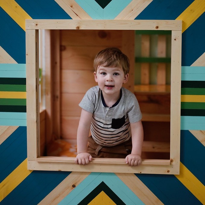 A child with Oasis Kids Explorers playing in playhouse.
