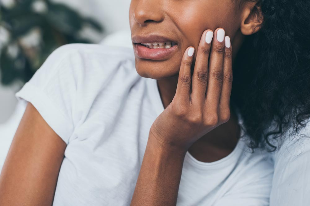 Young woman holding her cheek from tooth pain.