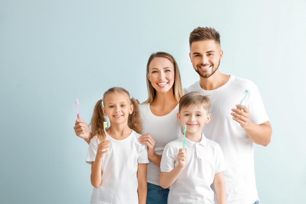 Young family holding their tooth brushes up in the air and smiling.