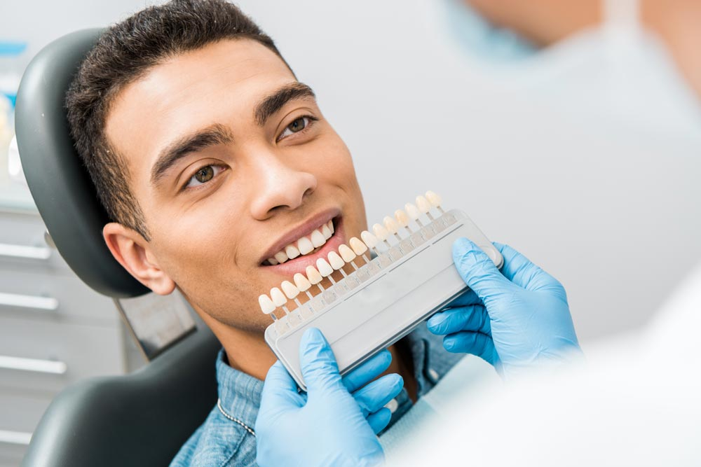 Young man on the dental chair choosing his new shade for teeth after a teeth whitening procedure in West Palm Beach.