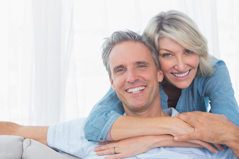 Middle aged couple smiling after receiving teeth in a day in Wellington.