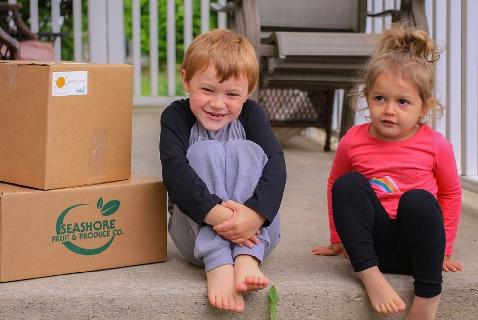 toddlers, a brother and sister on their front porch