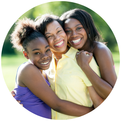 an african american mother being hugged by her two daughters