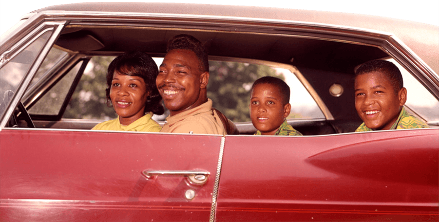 Family smiling in a retro red car