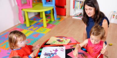 child minder watching two kids painting