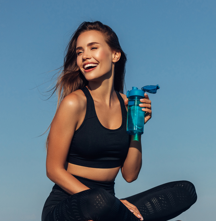 Stunning and fit woman sitting outside holding water bottle