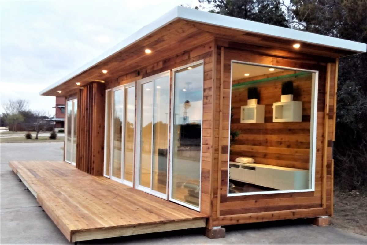 An exterior view of a modular home with wooden exteriors, large windows, and a wooden decking as a porch.