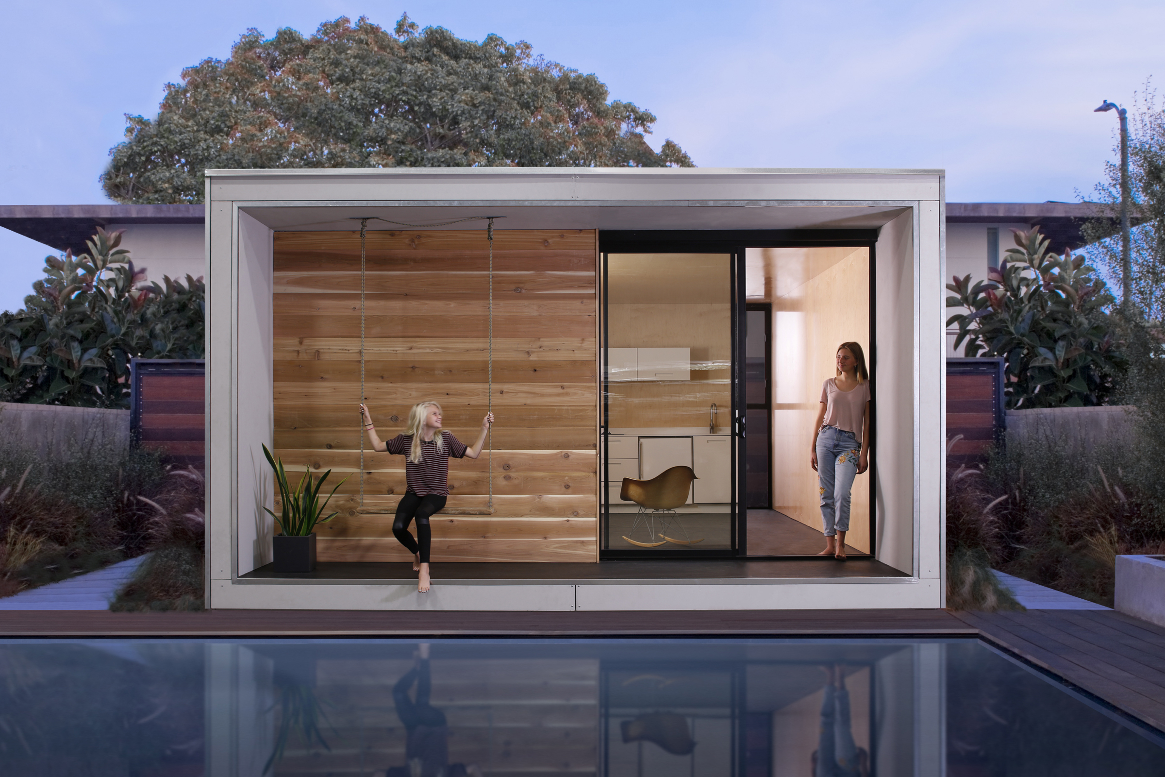 An exterior shot of a modular home illuminated at night with a girl on a swing and a pool in front.