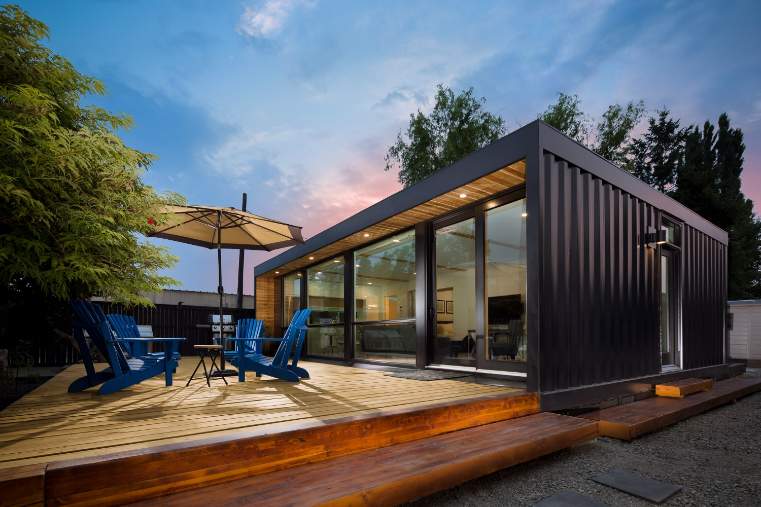 An exterior view of a black shipping container home with a porch, four blue chairs, an umbrella, and a grill.