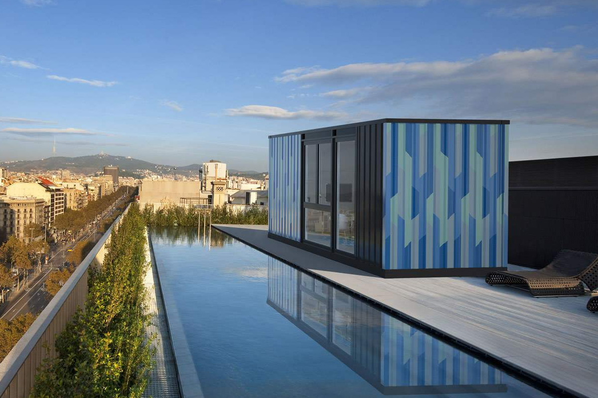 A shipping container home situated in the middle of a pool, with a city skyline present in the backdrop of the picture.