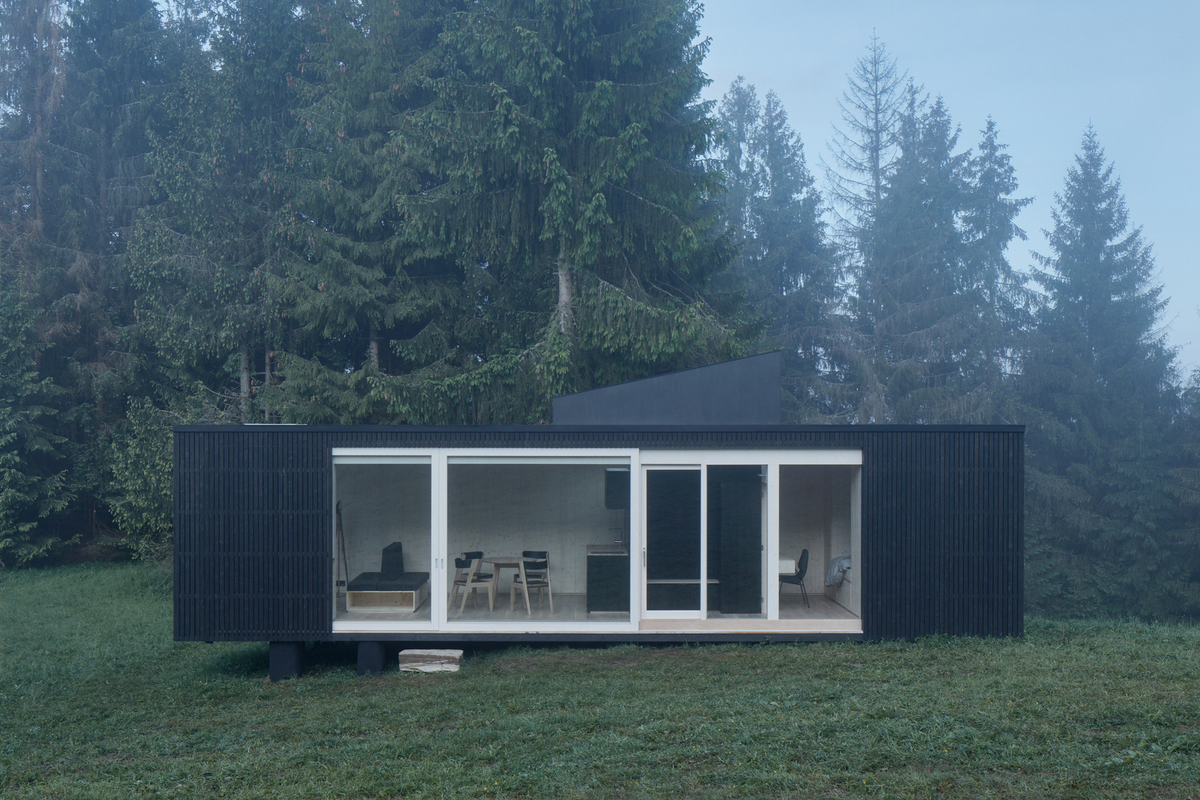 A rectangular modular home, with a black exterior and a large window, situated in a forest area with trees and grass all around.