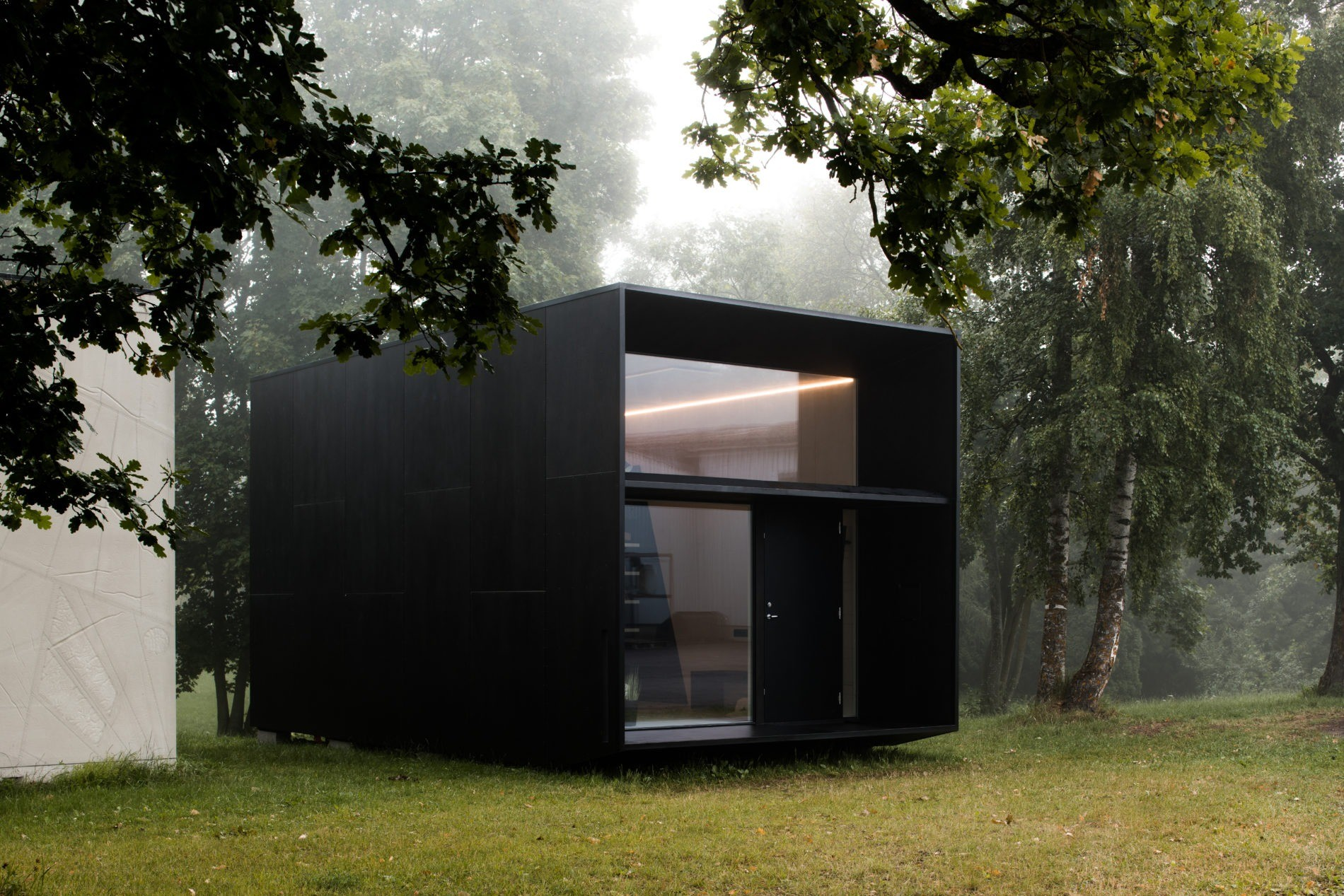 A white modular home in forest in the fall, with a large window visible, surrounded by trees and grass.