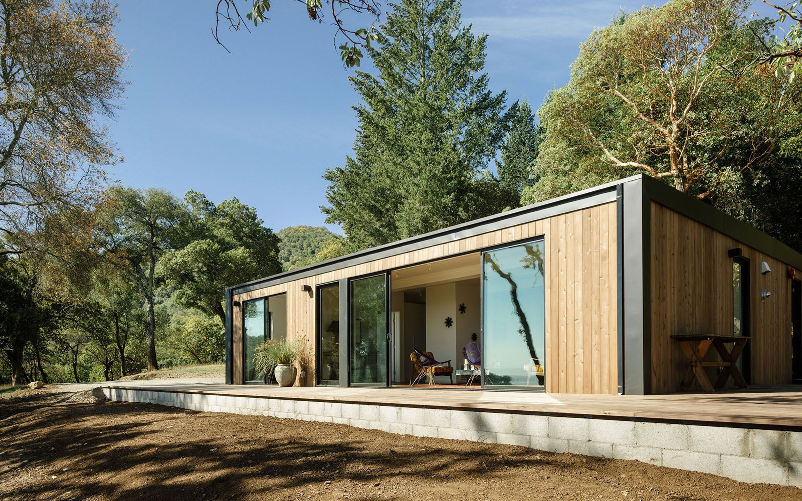 A modular home with vertical wooden panelling and two large windows, with a tree standing in front of the residence.
