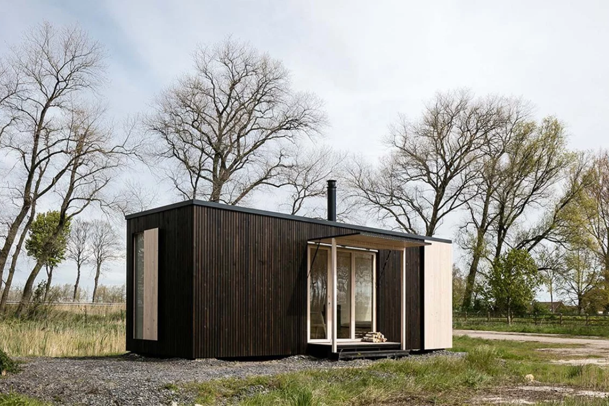 A frontal view of a black modular home, with large glass window, situated in the middle of a forest with trees and fog surrounding.