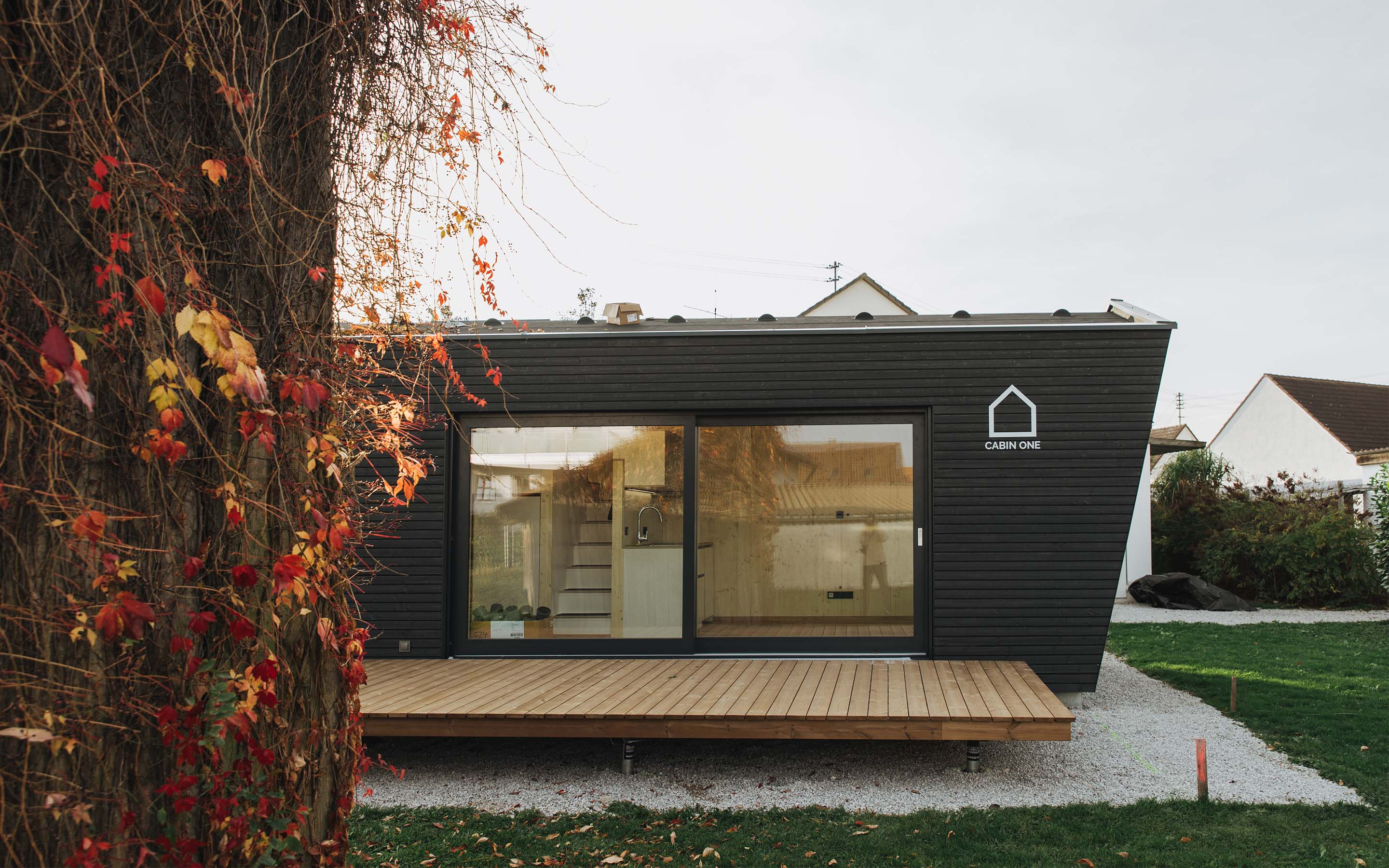 A close up of a modular home with black exterior material and a pitched roof, sitting in a field.
