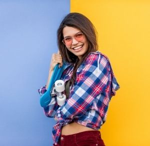 Happy skater girl in front of a colorful background.