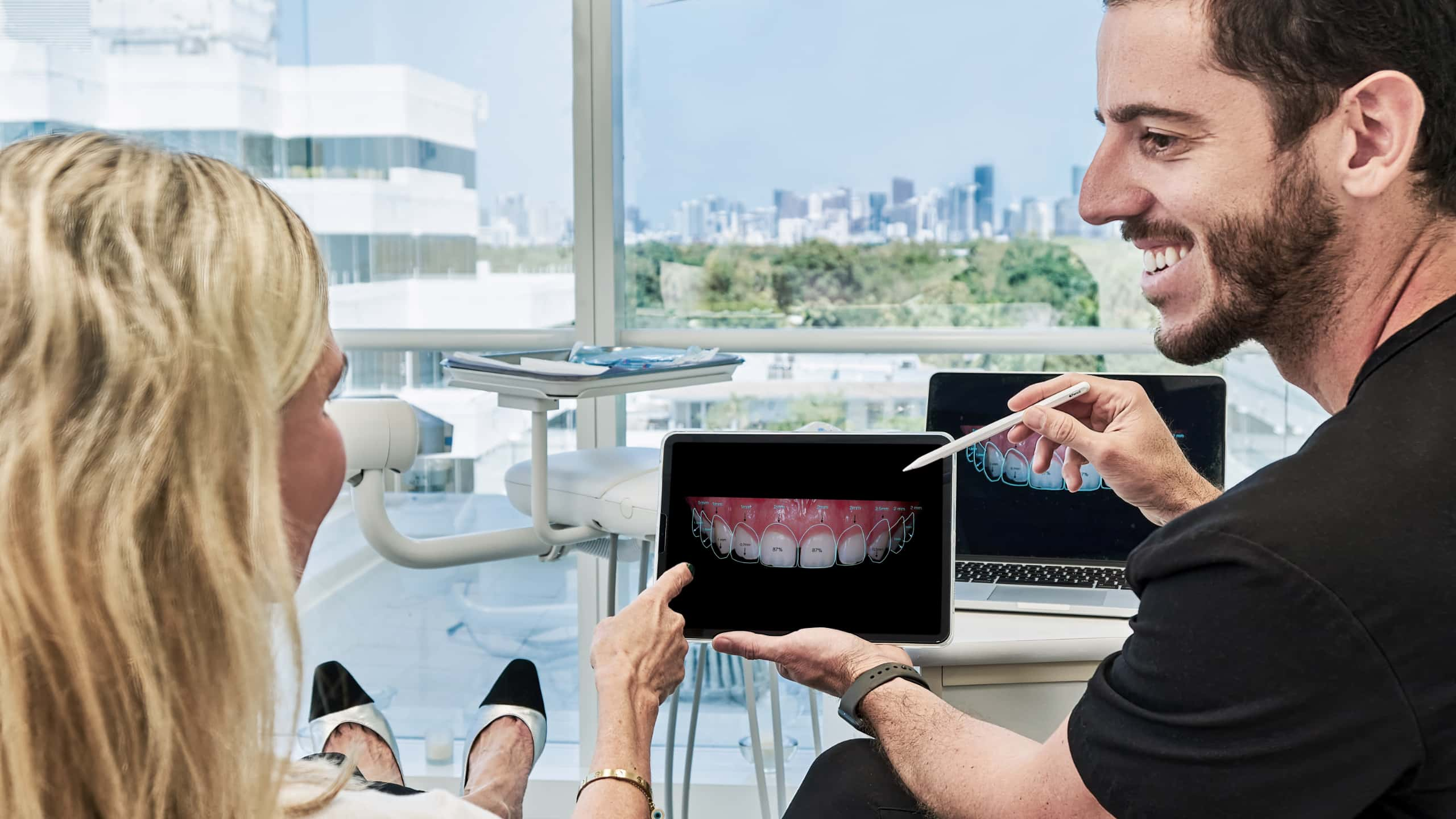 Man showing tablet with dental treatment simulation to a sited woman.