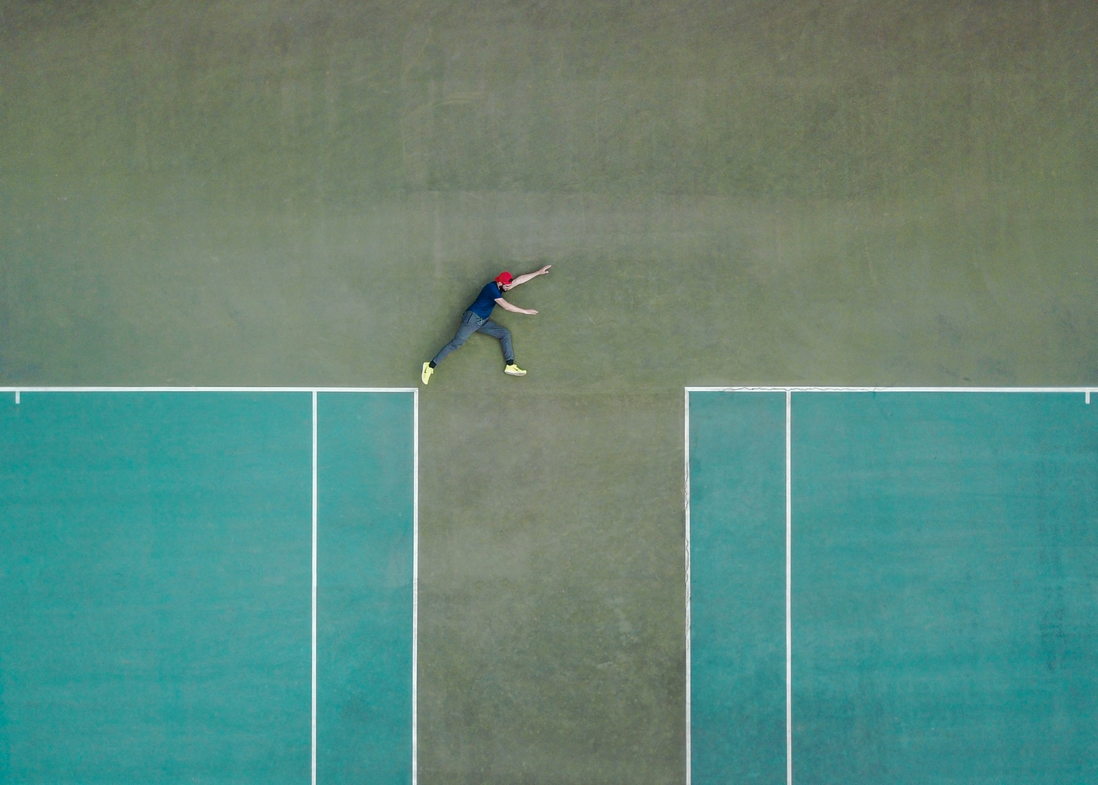 Person pretending to leap between two tennis courts