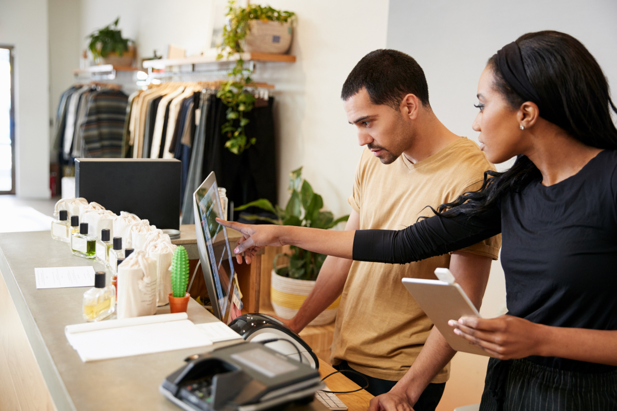 Retail manager training employee on Point of Sale system
