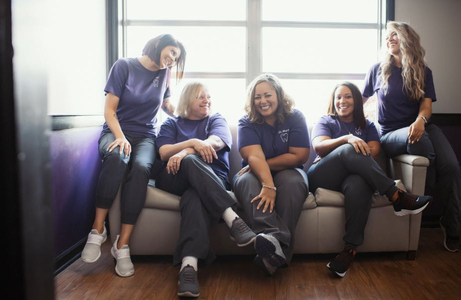 Photo of the Hometown DDS team on a couch smiling