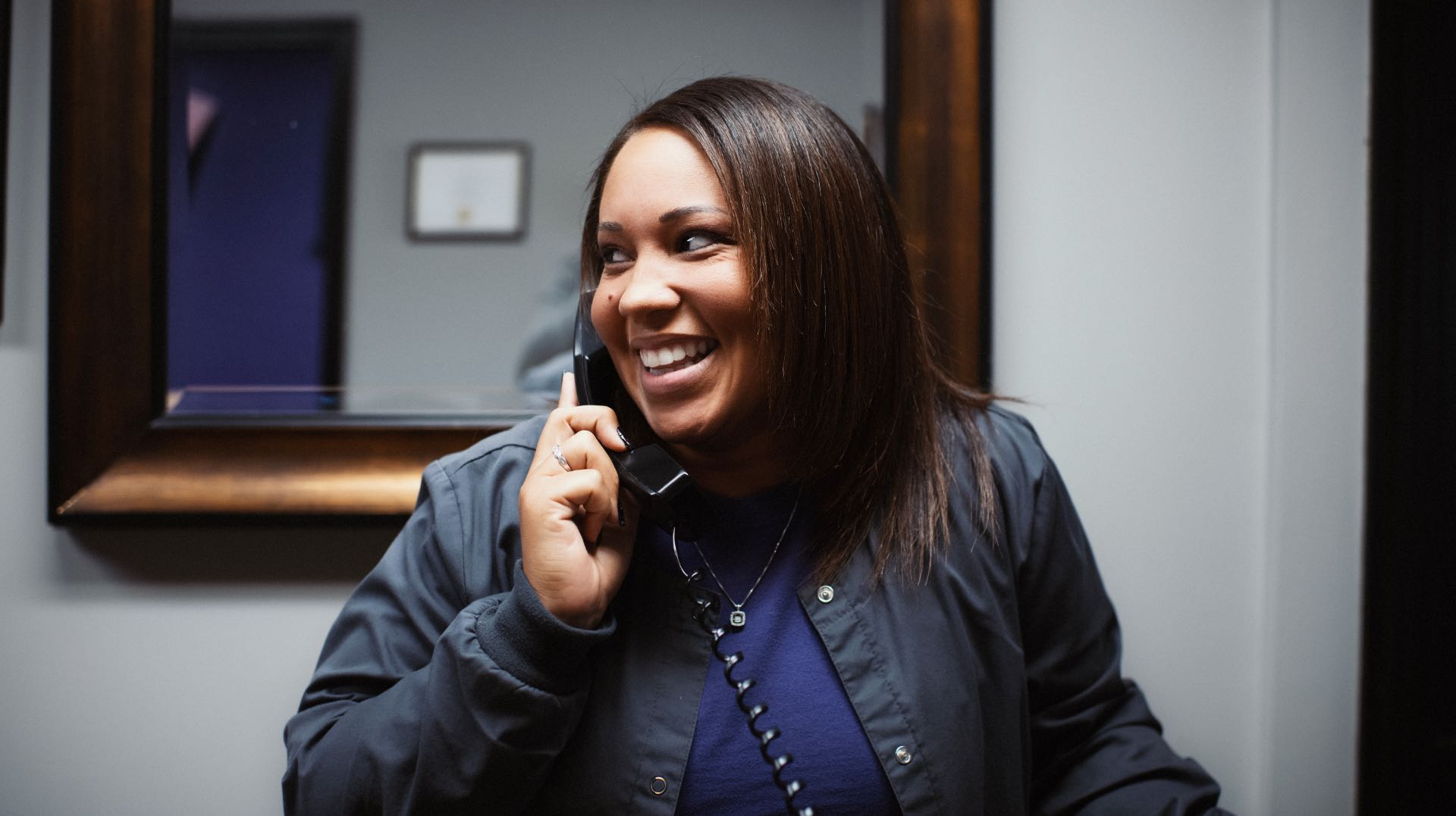 Photo of a team member on the phone with a patient smiling
