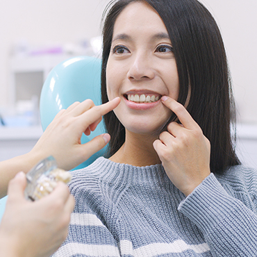 smiling patient pointing to teeth