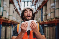 man in construction uniform holding tissue about to sneeze