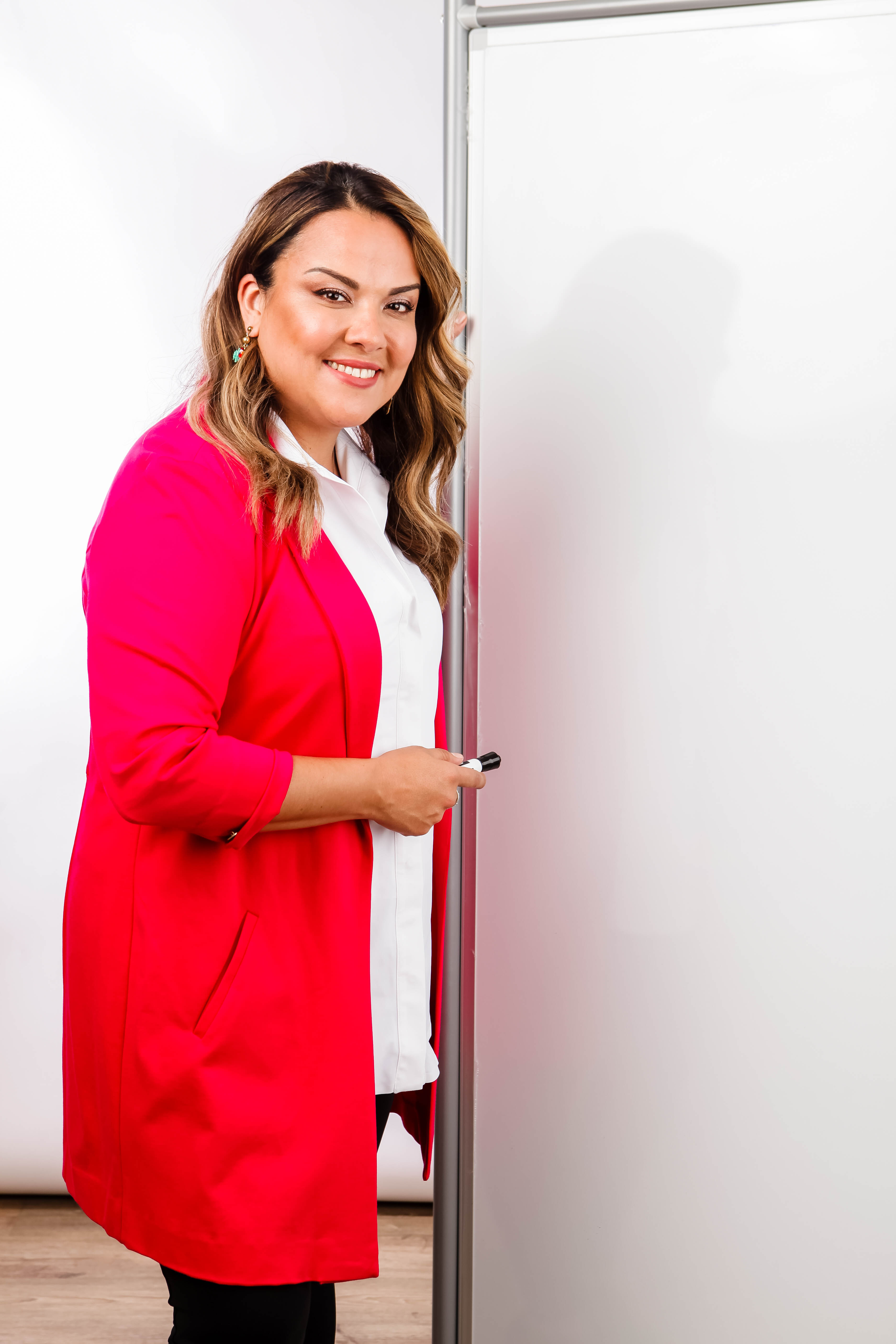 Karla Briones in a red blazer in front of a white board