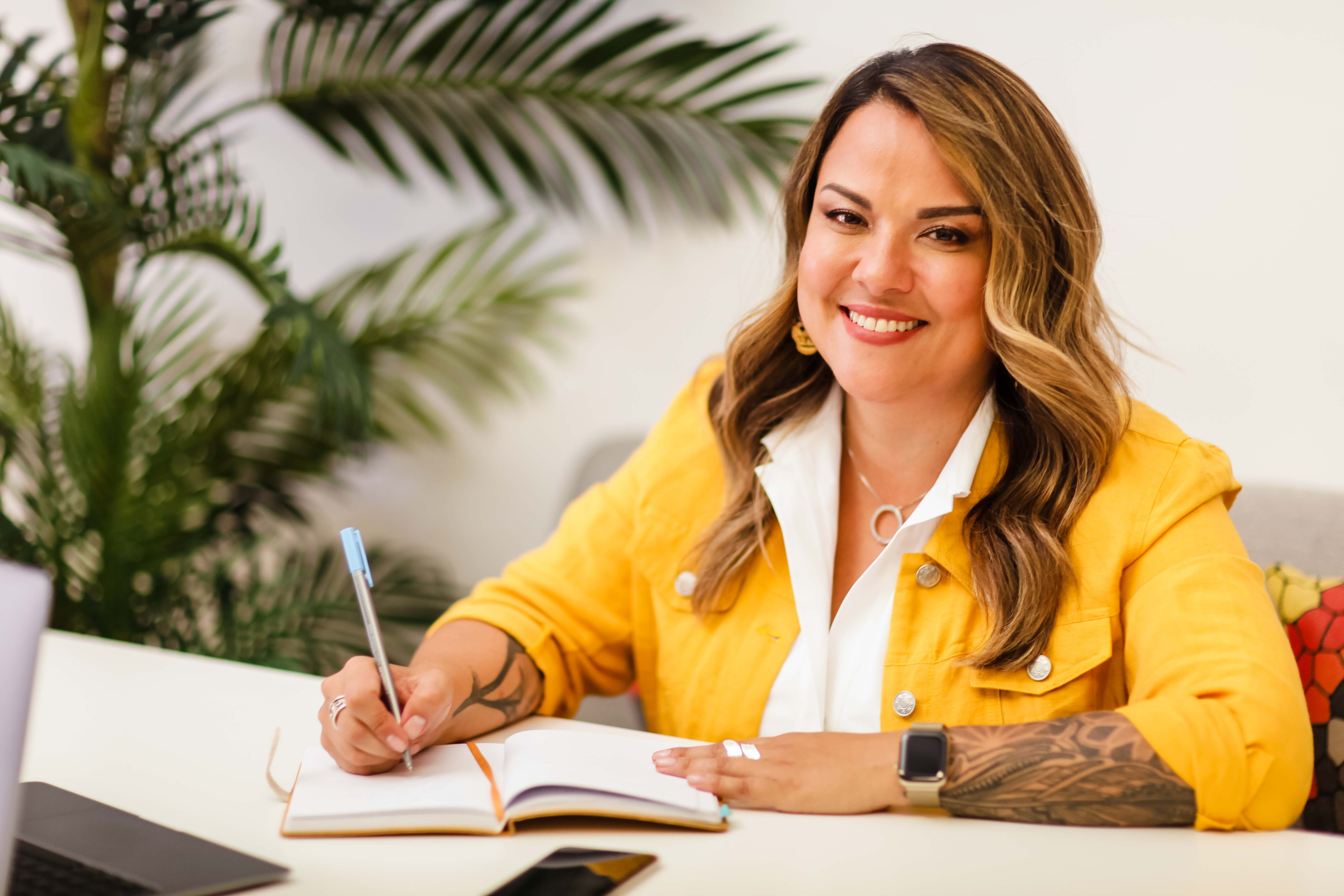 Karla Briones smiling and writing in a notebook