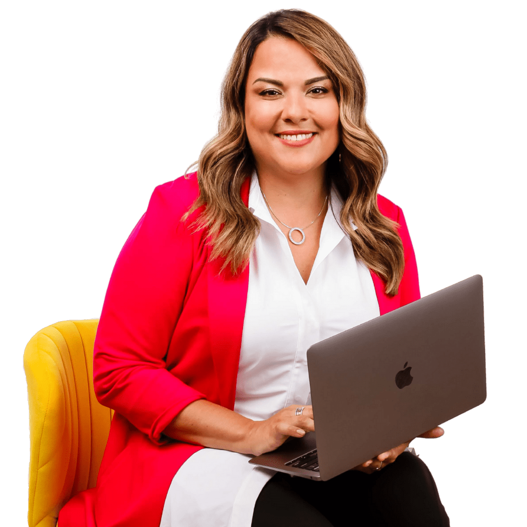 Karla Briones in a red blazer on her laptop and sitting on a yellow chair