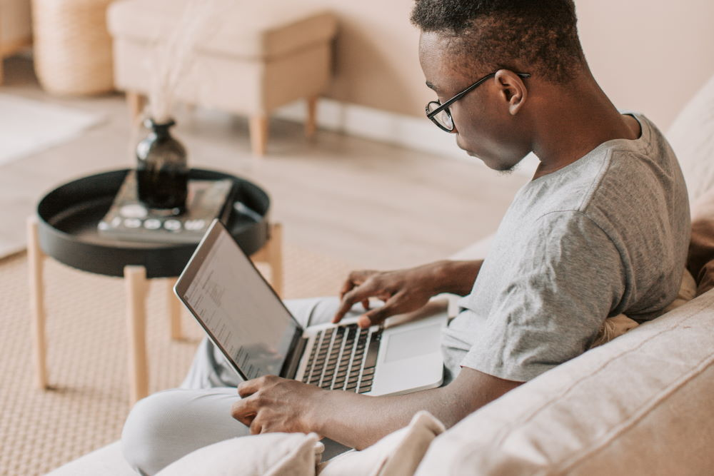 A young man watching Derek Prince on his laptop at home
