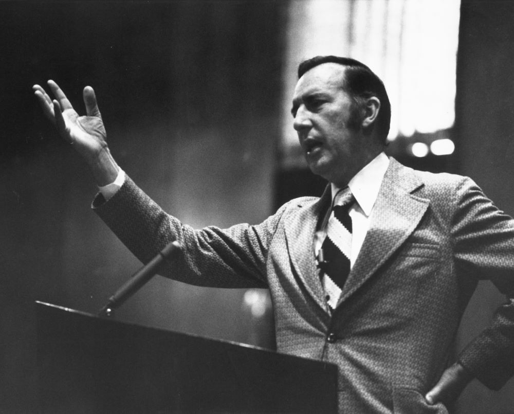 Derek Prince standing at the pulpit in church with his right hand raised, preaching to a crowd.
