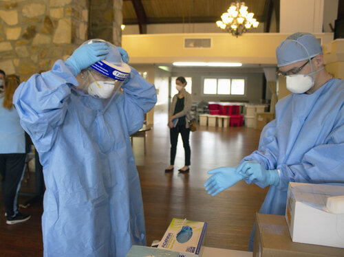 Two healthcare workers put on their protective gear.