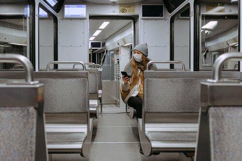 Woman wearing a mask on an empty train.