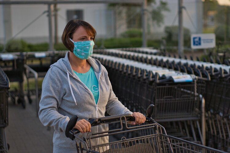 Citizen stands wearing a mask while entering a grocery store with a grocery cart.