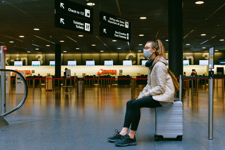 Travels sits on her suitcase in airport while wearing a mask